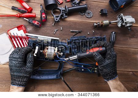 The Master Repairs A Broken Electrical Device: Drill, Cutter On A Wooden Table. Electric Tool Repair