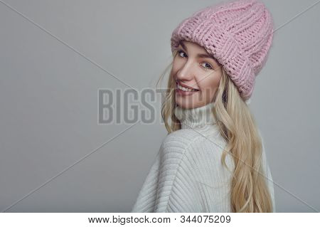Happy Young Woman With Long Blond Hair In Pink Knitted Winter Hat Looking At The Camera With A Grey