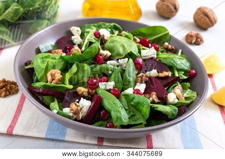 Salad With Young Spinach, Boiled Beets, Blue Cheese, Nuts, Cranberries In A Bowl On A Light Backgrou
