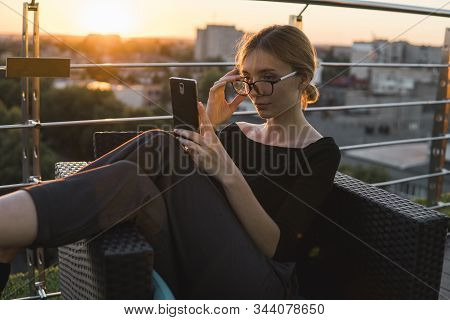 Young Business Woman Uses Phone. Good Looking Brunette Female Uses Online Banking On Smart Phone To