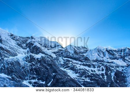 First Sun Rays Behind Grand Barrier In Himalayas, Annapurna Range, Nepal. Snowy Himalayas Mountains
