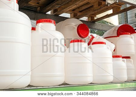 White Plastic Cans With Red Lids On A Rack Stillage. Domestic Tanks For Drinking Water.