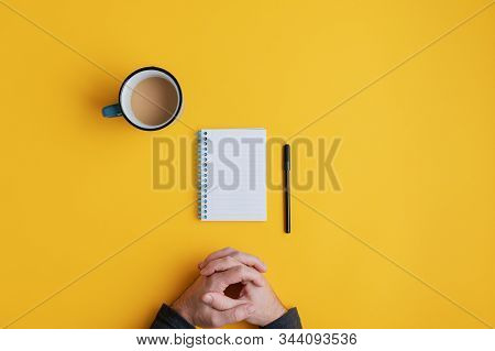 Top View Of A Man Ready To Write In A Blank Spiral Notebook With Black Marker. Over Yellow Backgroun