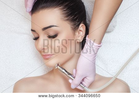 poster of The cosmetologist makes the procedure Microdermabrasion of the face skin of a beautiful woman in a beauty salon.Cosmetology and professional skin care.