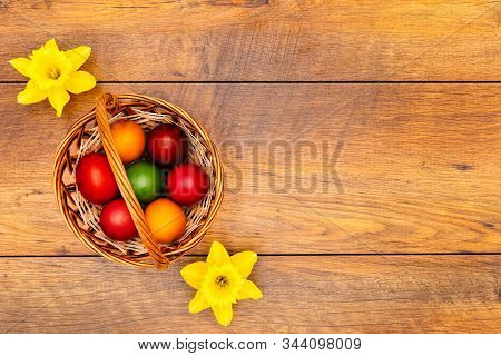 Seven Colourful Easter Eggs In Pastel Colours In The Basket And Two Yellow Daffodils On Vintage Recl