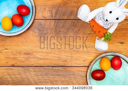 Six Colourful Easter Eggs On Two Plates In Pastel Colours And Easter Bunny Holding Carrot On Vintage
