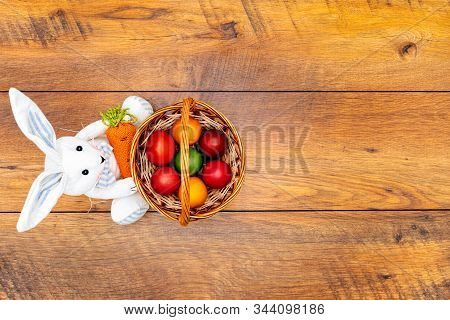 Seven Colourful Easter Eggs In Pastel Colours In The Basket And Easter Bunny Holding Carrot On Vinta