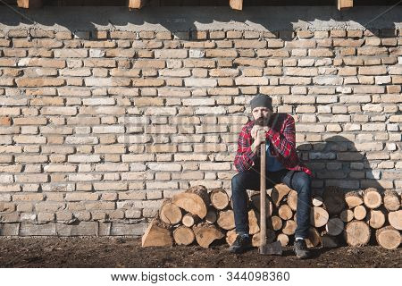 The Sad And Tired Lumberjack Worker With Axe Is Sitting On Firewood On Brick Wall.
