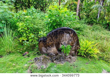 A Giant Prehistoric Megalithic Stone Coin Or Money Rai, Overgrown Under Trees In Jungle. Yap Island,