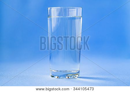 Glass Of Water On A Blue Background Close-up