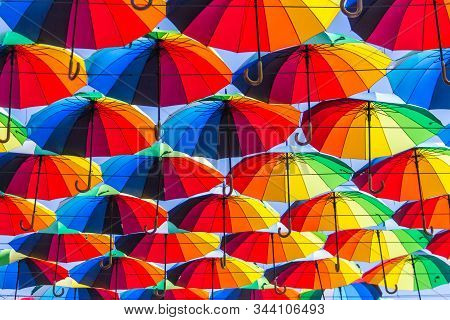 Street Art Of Many Multicolored Decorative Umbrellas Along Street Passage Covering The Sky.