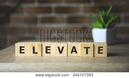 Elevate Word Written On Wood Block, Business Concept.