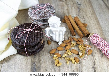 Chocolate Ginger Biscuits Bandaged With Red-and-white Thread With Thread, Cardamon And Nuts Laid Out