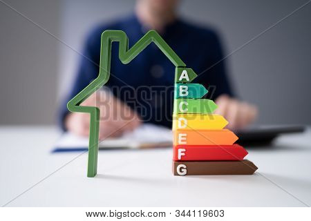Midsection Of Businessman Calculating Invoice With Energy Efficient Chart On House Model In Office