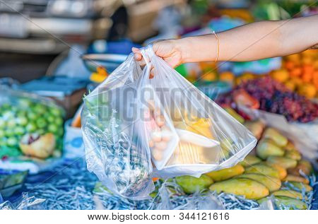 Woman's Hand Holding Fruit Bags
