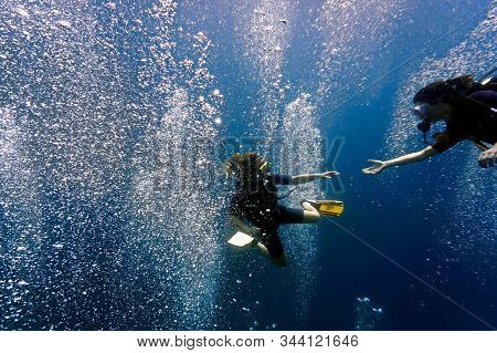 Underwater Photo Of Two Scuba Girl Friend Reaching Out To Each Other Surrounded By Magical Air Bubbl