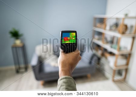 Person Hand Using Infrared Thermal Camera In Living Room