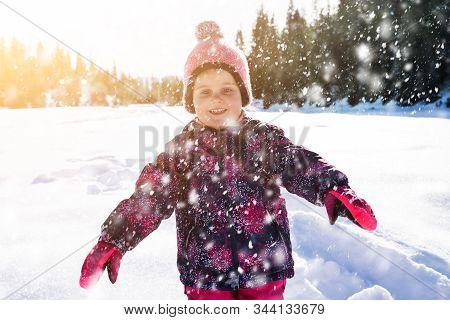 Joyful Adorable Girl Walking With Woolly Hat On Snowy Landscape