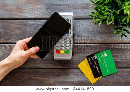 Contactless Payment, Nfc Technology. Hand Hold Phone Near Terminal On Dark Wooden Background Top-dow