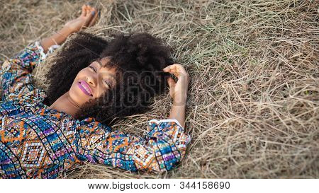 Portrait Of Young Afro Hairstyle Woman Relaxing Lying On The Ground. Outdoor Rest And Relaxation In