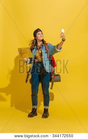 Taking Selfie Or Vlog. Portrait Of A Cheerful Young Caucasian Tourist Girl With Bag In Jeans Clothes