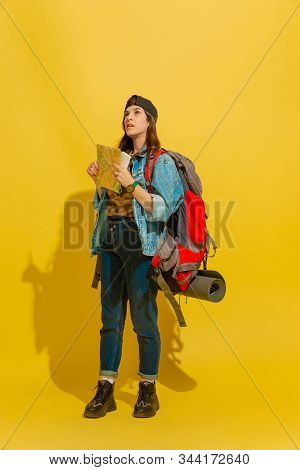 Dreamful Looking Up For Way. Portrait Of A Cheerful Young Caucasian Tourist Girl With Bag Isolated O