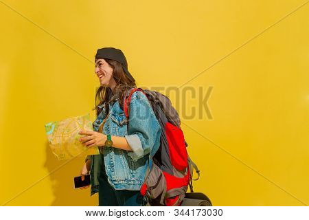 Smiling, Looks At Side. Portrait Of A Cheerful Young Caucasian Tourist Girl With Bag In Jeans Clothe