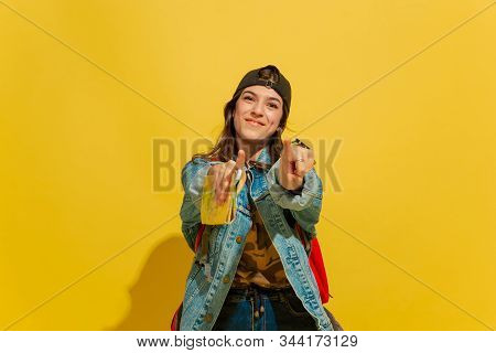 Smiles, Pointing On. Portrait Of A Cheerful Young Caucasian Tourist Girl With Bag In Jeans Clothes I