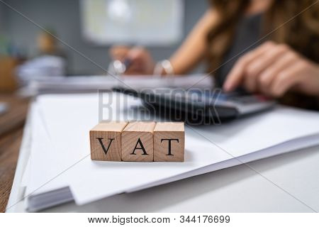 Close-up Of Vat Wooden Blocks With Businessperson Calculating Bill