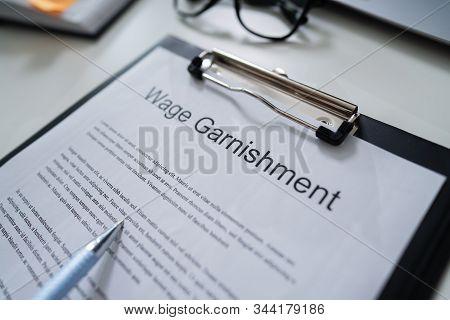 Person Reading  Wage Garnishment Documents At Desk