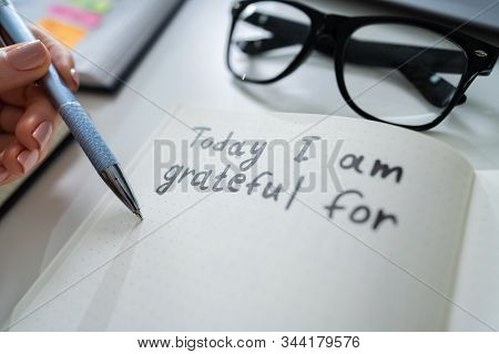 Close-up Of A Person Writing I Am Grateful For Text In Notebook With Black Marker