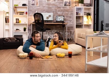 Couple Sitting On The Floor And Watching Tv In Their Living Room