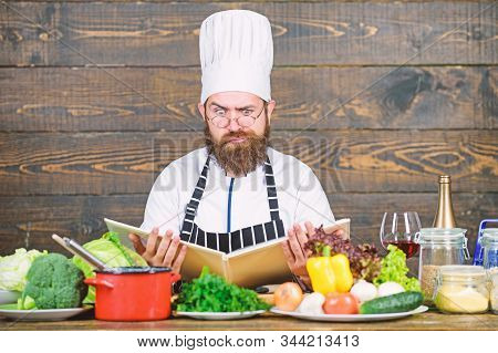 Man Bearded Hipster Read Book Recipe Near Table Fresh Vegetables. Culinary Arts. Recipe To Cook Heal
