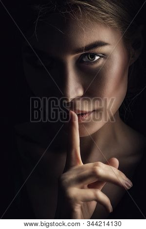 Girl Shows A Sign Of Silence. Face On A Dark Background. Dont Talk Concept