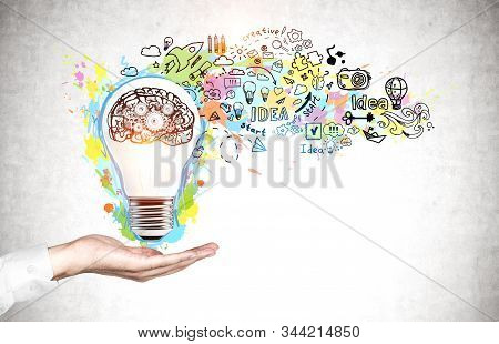 Hand Of Businessman Showing Lightbulb Near Concrete Wall With Colorful Creative Idea Sketch Drawn On