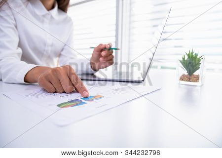 A Business Woman Sitting In Front Of A Laptop In The Office.data Analysis Concept From Summary Graph