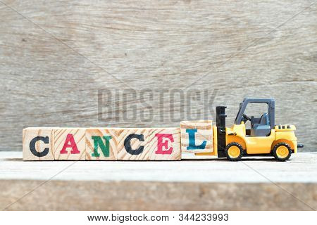 Toy Forklift Hold Letter Block L To Complete Word Cancel On Wood Background