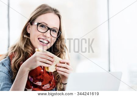 Businesswoman working while eating sandwich in her desk in office