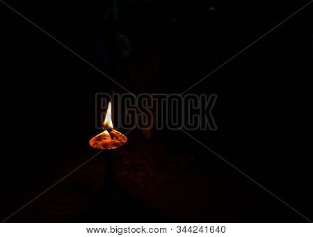 Soil Or Clay Lamp Radiating Light In Dark. Concept Of Removing Darkness With A Flame. This Types Of