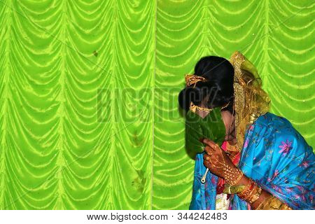 A Beautiful Happy Indian Bride Holding Betel Leaf , Bengali Bride In Traditional Wedding Saree. Copy