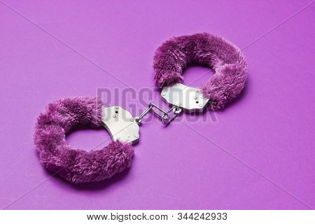 Handcuffs For Sex Games On Purple Background. Sexual Bdsm Toy. Fetish, Erotic Concept.