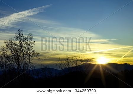 Sunset Over The North Carolina Mountains With Tree Silhouettes And Contrail In The Sky