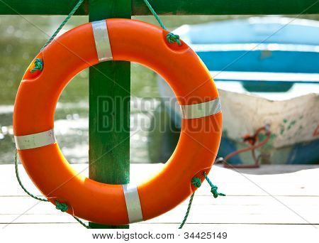 Lifebuoy at the mooring and the boat on a background