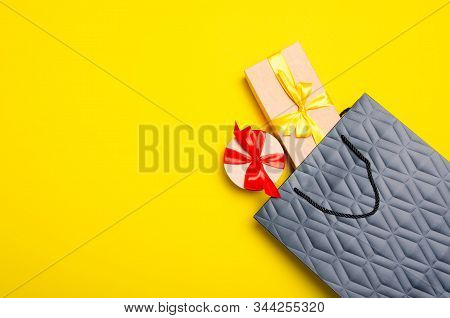Black Shopping Paper Bag With Gift Boxes On Yellow Background, Top View