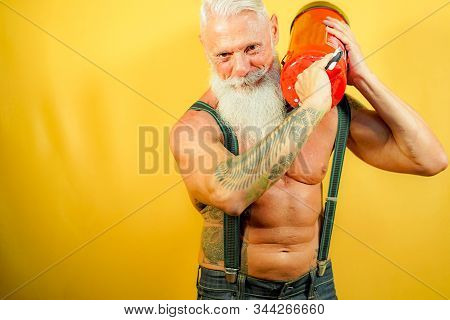 Fitness Man Showing His Strenght. Tattoo Male Model With White Long Beard In Front Of A Yellow Backg