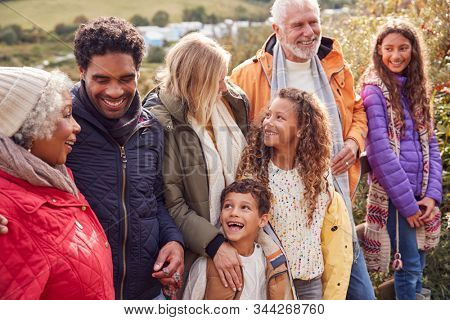 Active Multi-Generation Family On Winter Beach Vacation Resting By Gate
