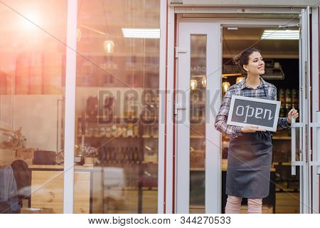 Mixed Race Woman Worker Or Store Owner With Standing In The Doorway Of Her Grocery Shop Looking Asid