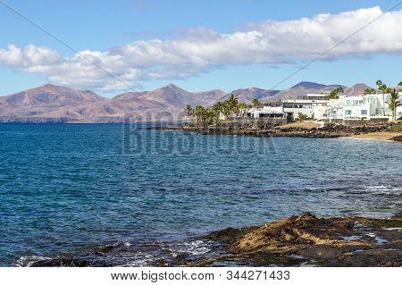 Rocky Coast Of Puerto Del Carmen At Canary Island Lanzarote With Lava Rocks And Blue Water In The Fo