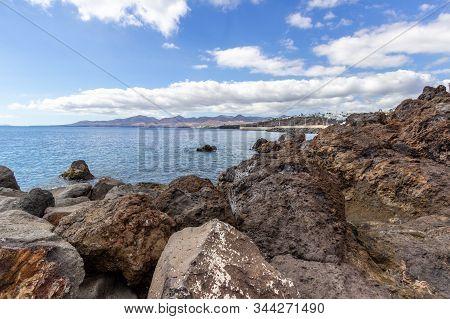 Big Lava Rocks On The Coastline Of Puerto Del Carmen At Canary Island Lanzarote, Spain. The Sky Is B