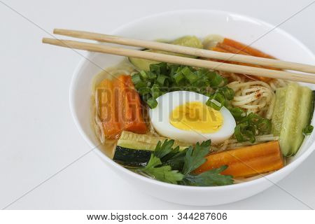 Traditional Asian Soup With Tofu Cheese, Noodles, Carrots And Zucchini On White Background, This Dis